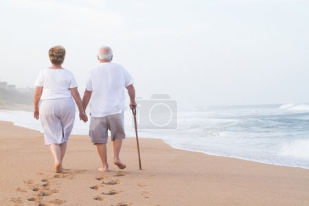 Photo for Senior couple hand in hand walking on beach - Royalty Free Image