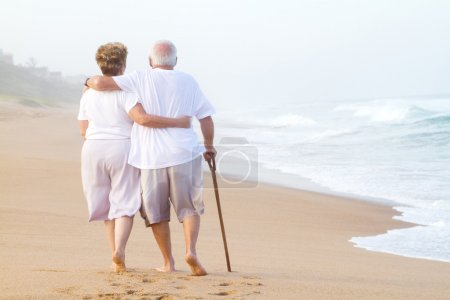 Photo for Elderly couple walking on beach - Royalty Free Image