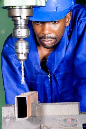 Photo pour Machine afro-américaine travaillant sur une machine à outiller - image libre de droit