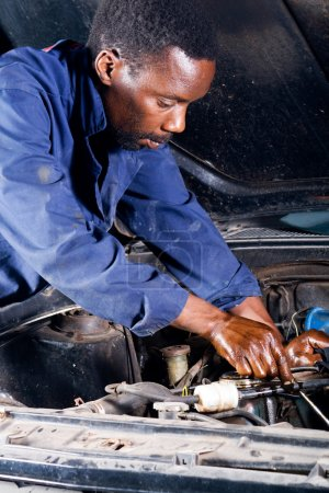 African amercian fixing car in garage