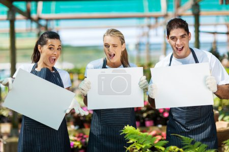 Group of funny nursery workers with white board in greenhouse