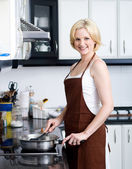 Happy woman cooking in kitchen