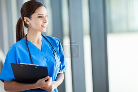 Beautiful young female medical intern looking outside window