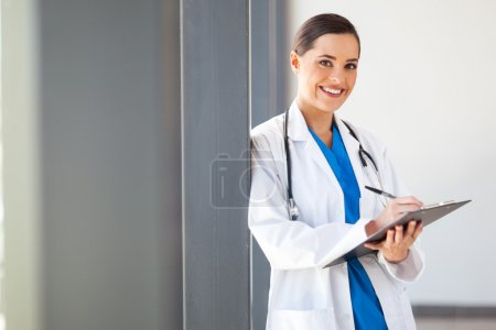 Female medical worker writing report in office