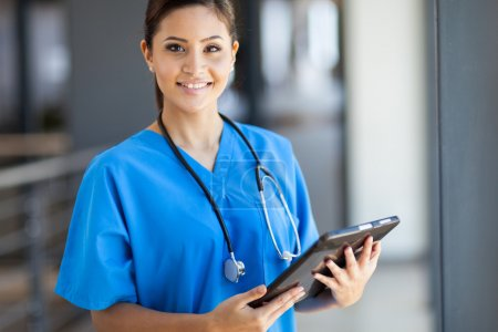Beautiful young female medical intern with tablet computer in office