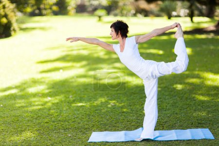 Elegant middle aged woman doing yoga outdoors