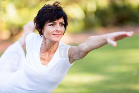 Photo for Healthy middle aged woman stretching outdoors - Royalty Free Image