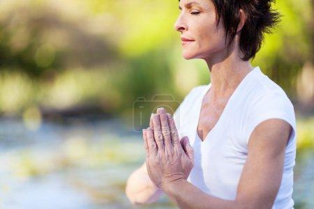 Foto de Mujer de mediana edad haciendo yoga meditacion - Imagen libre de derechos