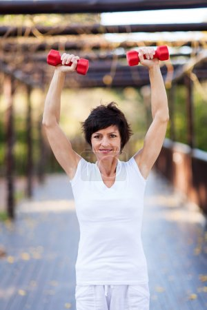 Active middle aged woman working out with dumbbells