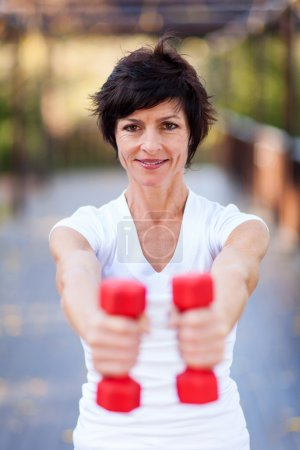 Active middle aged woman exercise with dumbbells
