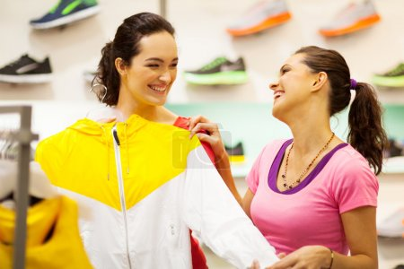 Two young women shopping for sportswear in mall