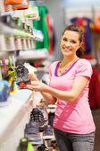 Mujer joven feliz elegir zapatos deportivos para comprar en la tienda