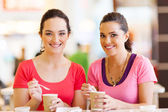 Two women friends having drinks in cafe