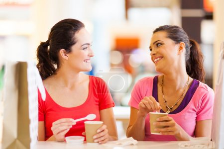 Two happy friends having drinks in cafe
