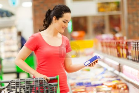 Photo for Young woman doing grocery shopping in supermarket - Royalty Free Image