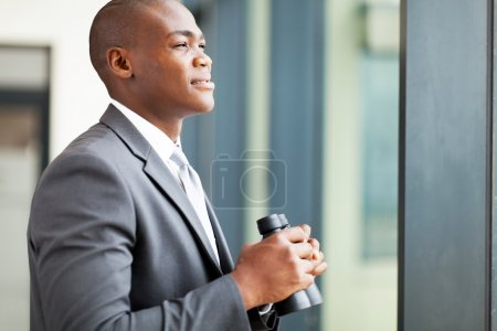 Determined african american businessman with binoculars