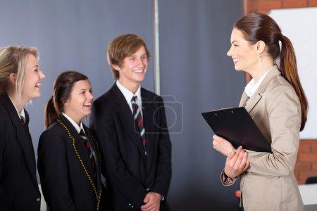 Happy high school teacher talking to students in classroom