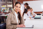 Attractive female school teacher in classroom
