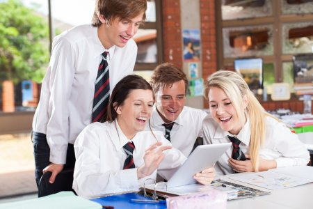 Group of happy high school students using tablet computer