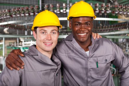 :two friendly industrial workers colleagues in factory