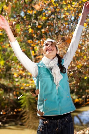 Photo for Happy woman throwing autumn leaves in forest - Royalty Free Image
