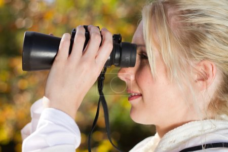 Photo for Young woman using binoculars in autumn forest - Royalty Free Image