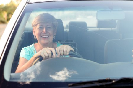 Senior female driver inside car