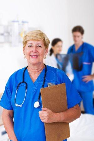 Happy female senior nurse and colleagues in hospital ward