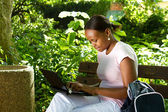 Female african college student using laptop outdoors