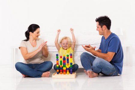 Happy little girl playing toys with parents on bedroom floor