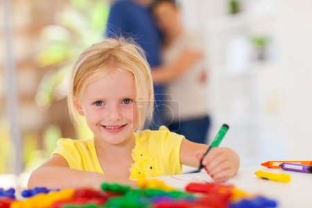 Happy little girl drawing in front of parents at home