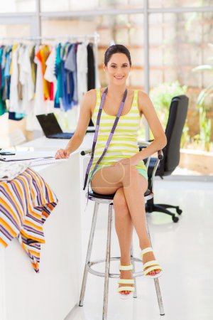 Attractive young female fashion designer sitting in her office