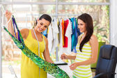 Happy fashion designer showing a dress to her customer
