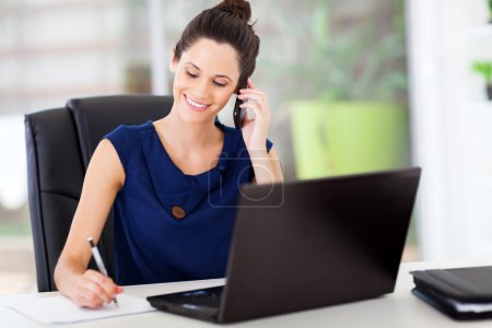 Photo for Cute young office worker talking on cell phone in office - Royalty Free Image
