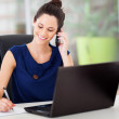 Cute young office worker talking on cell phone in ...