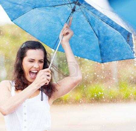 Photo pour Espiègle jeune femme tenir le parapluie sous la pluie - image libre de droit