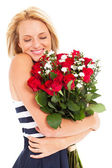 Pretty woman hugging bunch of red roses