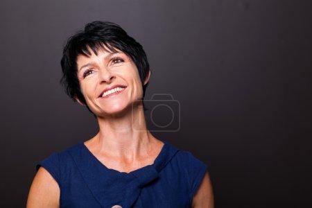Foto de Retrato de mujer edad media optimista sobre fondo negro - Imagen libre de derechos