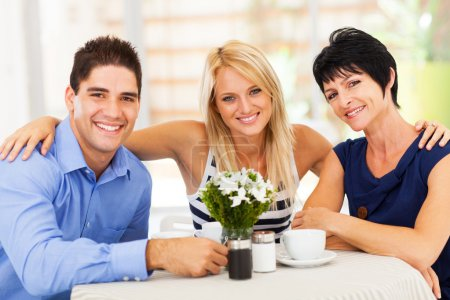 Happy young man with wife and mother-in-law in cafe