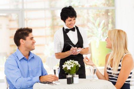 Photo pour Sympathique serveuse âgée milieu prenant la commande du client au restaurant - image libre de droit
