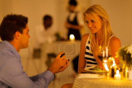 jeune homme propose à sa petite amie dans un restaurant tout en ayant un dîner aux chandelles