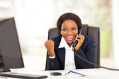 Young african american businesswoman receiving excited news in office