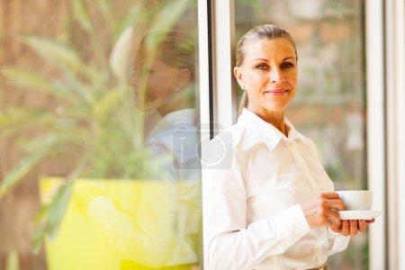 Photo pour Jolie dirigeante d'entreprise au bureau avec café - image libre de droit