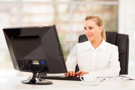 Middle aged female office worker working on computer