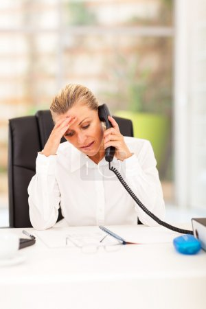 Worried senior businesswoman talking on the phone in office