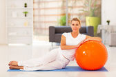 Elegant middle aged woman sitting on mat with exercise ball