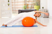 Middle aged woman doing fitness on exercise ball at home