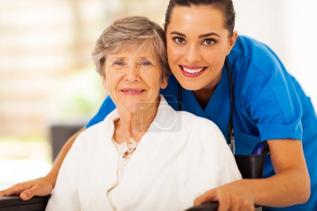 Photo for Happy senior woman on wheelchair with caregiver - Royalty Free Image