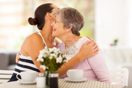 Photo for Young woman hugging senior mother when visiting her - Royalty Free Image