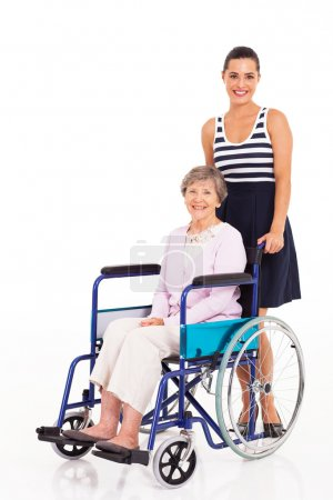 Caring daughter pushing senior mother on wheelchair on white background